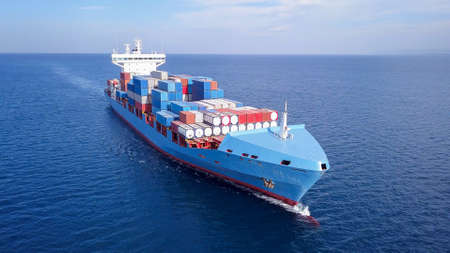 ULCV container ship sails on open water fully loaded with containers and cargo.