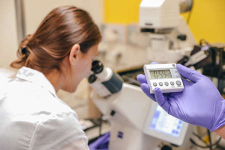 Scientists perform scientific research with the help of a microscope in the laboratory.