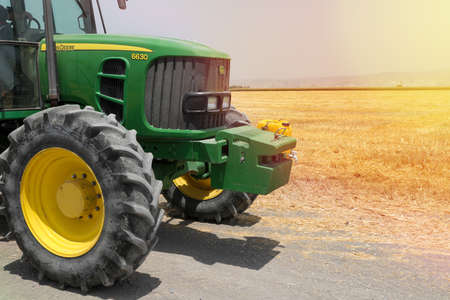 North district, Israel - July 01, 2020: Modern John Deere Tractor and agriculture field in the background. Agriculture concept.