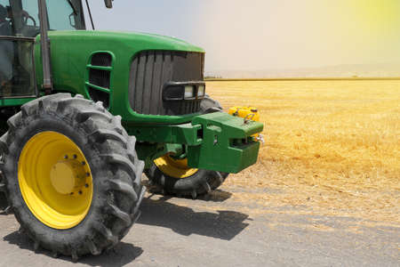 Tractor Wheel covered in mud and plowing field in the background. Agriculture concept. 写真素材