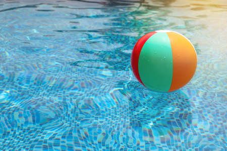 Beach ball in pool. Colorful inflatable ball floating in swimming pool, summer vacation concept. 스톡 콘텐츠
