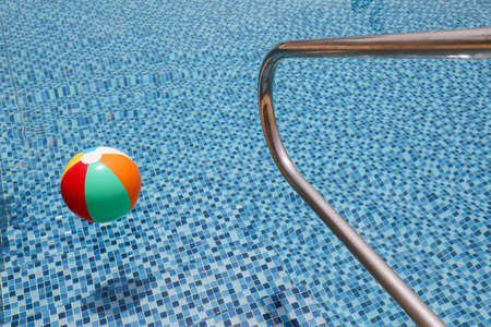 Grab bars ladder in a blue swimming pool. 스톡 콘텐츠