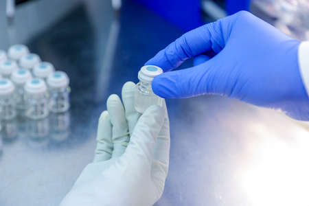 Hand with medical glove holding a bottle vaccine from ice storage. Medication treatment at nitrogen freeze.
