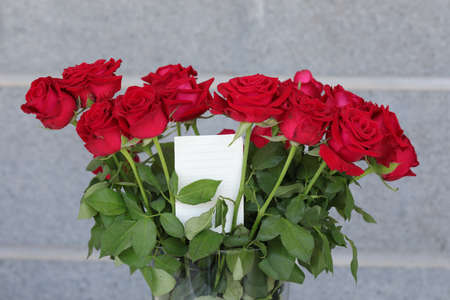 Bouquet of red roses in a vase and a white note for writing a greeting.