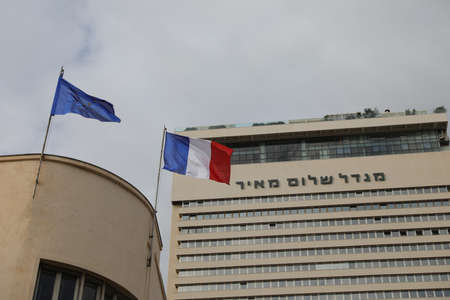 TEL AVIV, ISRAEL - November 23, 2020: Shalom Tower (Shalom Meir). Iconic skyscraper in Tel Aviv. Flags of France and the European Union upfront. 에디토리얼
