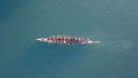 Dragon Boat team rowing together. Teamwork on Dragon Boat at sea. 스톡 콘텐츠