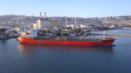Oil tanker ship loading in port. Fuel tanker ship docked in industrial area. LPG tanker.