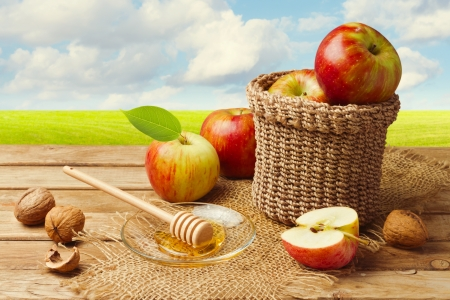 rustic food: Apples with honey on wooden table over green meadow