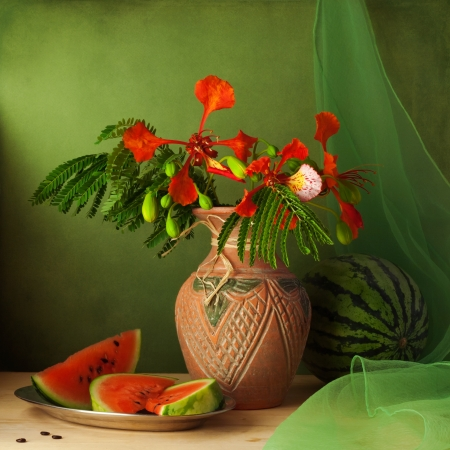 Still life with water melon and red flowers over green background