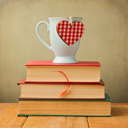 Coffee mug with heart shape on vintage books photo