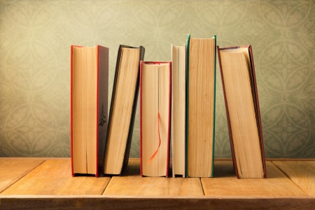 Vintage books on wooden table over retro wallpaper background Stock Photo - 20959737