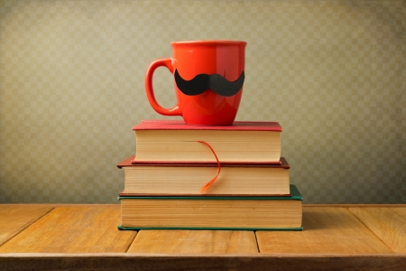 Vintage books and cup with mustache on wooden table over retro background photo