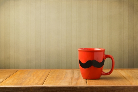 Red cup with paper mustache on wooden table over retro wallpaper Stock Photo - 20959741