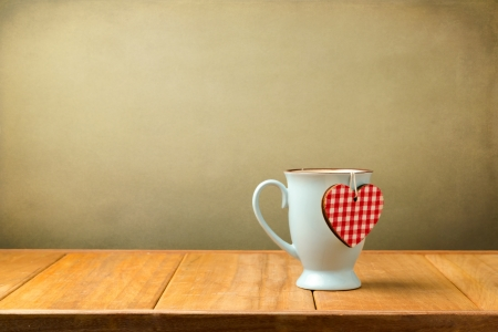 Coffee mug with heart shape on wooden table
