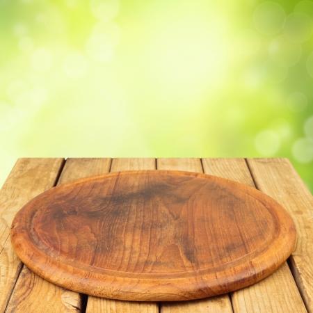 Houten plank op houten tafel over bokeh tuin achtergrond Stockfoto