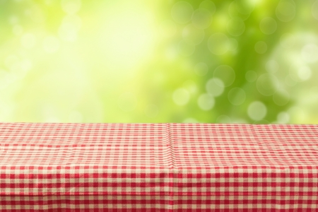 picnic cloth: Empty table coved with tablecloth over bokeh garden background Stock Photo