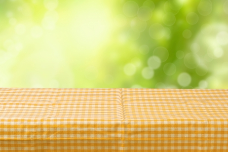 Empty table coved with tablecloth over bokeh garden background photo