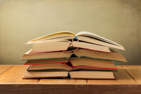 Stack of open old books on wooden table over grunge background Stock Photo