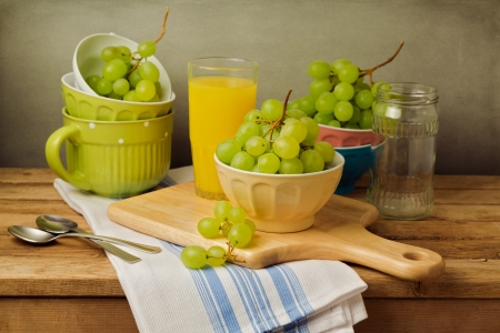 Still life with grapes on wooden table over grunge background Stock Photo