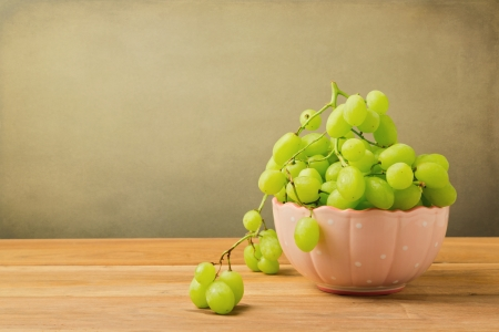 Green grapes in bowl on wooden table over grunge background Stock Photo - 21197548