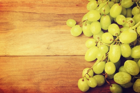 Retro style grunge background grapes on wooden vintage board