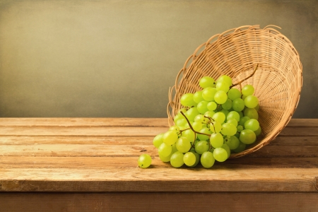 Grapes in basket on wooden table over grunge background Stock Photo - 21197551