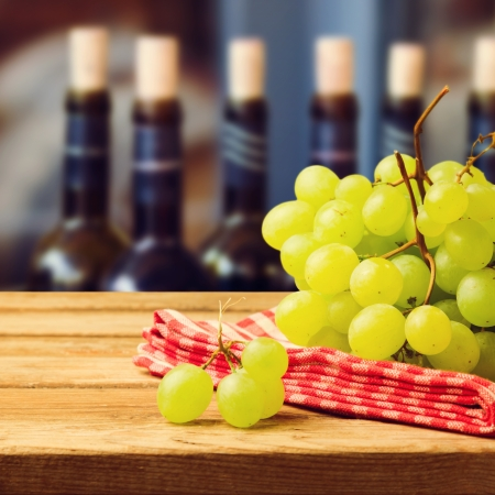 red tablecloth: Grapes on tablecloth over wine bottles