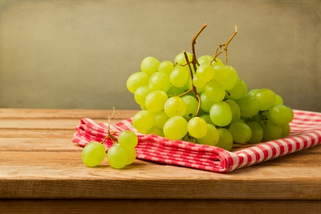 Grapes on checked tablecloth on wooden table over grunge background Stock Photo - 21197554
