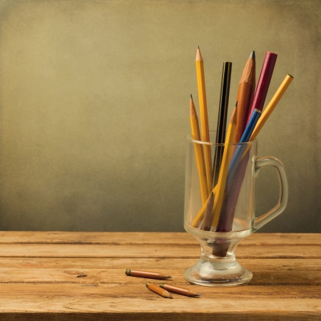 Vintage pencils in glass on wooden table over grunge background Stock Photo - 21186709