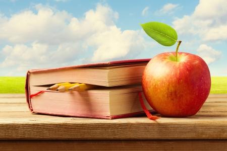 paisaje vintage: Apple y libro con los l�pices en la mesa de madera sobre el paisaje hermoso. Volver al concepto de escuela