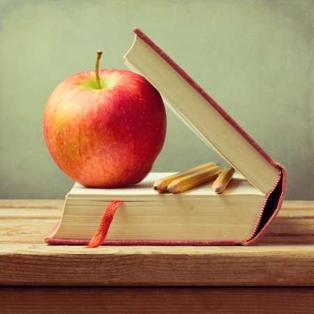 sceince: Old book and apple on wooden table over grunge background. Back to school concept