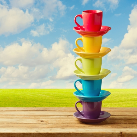 Rainbow color cups on wooden table over beautiful sky and meadow. Stock Photo - 21197575