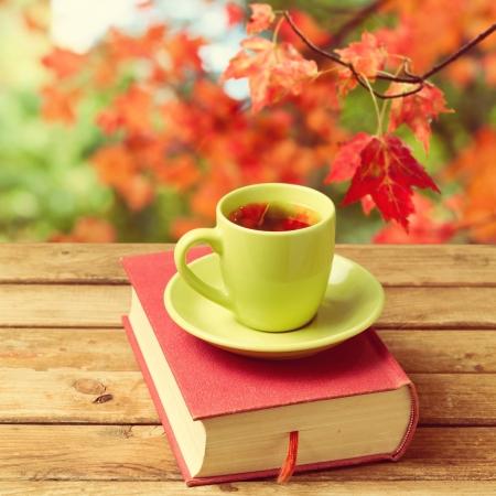 Kopje thee met herfstbladeren reflectie op boek op houten tafel