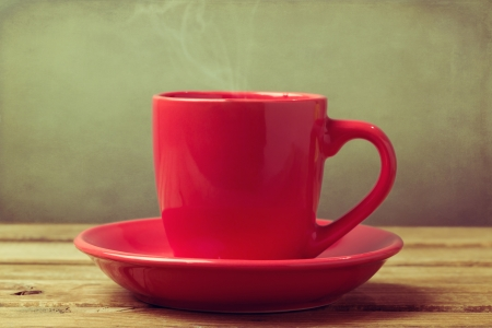 Close up of red coffee cup on wooden table over grunge background
