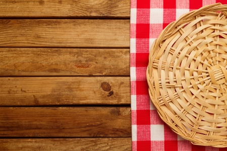Background with wooden deck board, checked tablecloth and wicker plate Stock Photo - 21197580