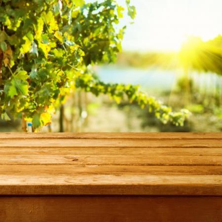 ぶどう畑の背景のボケ味を空の木製デッキ テーブル