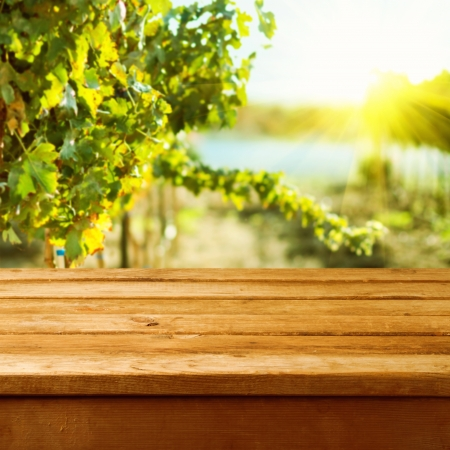 deck: Empty wooden deck table over vineyard bokeh background