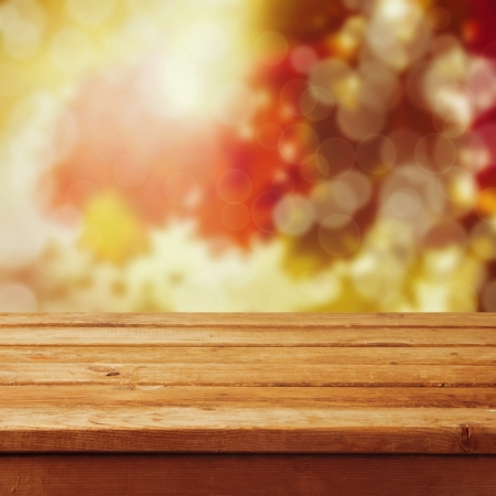 Empty wooden table over autumn leaves bokeh background. Ready for product montage