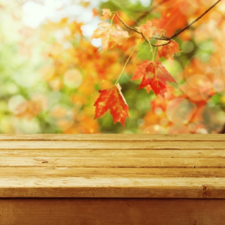 Beautiful autumn background with empty wooden deck table. Ready for product montage display.