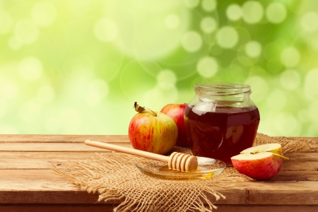Honey and apples on wooden table over bokeh garden background