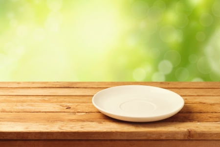 plate: Empty plate on wooden table over bokeh background Stock Photo