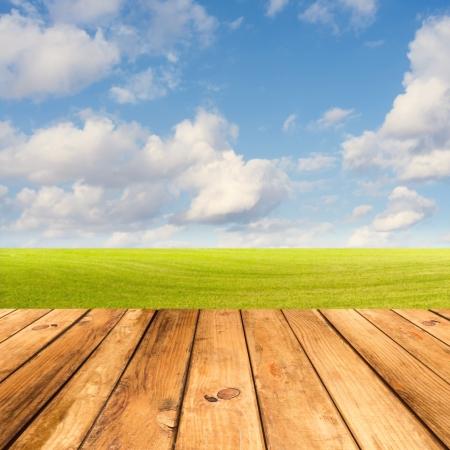 Houten dek tafel over mooie weide met blauwe hemel