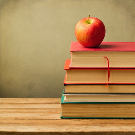 Old books and apple on wooden table over grunge background Stock Photo - 21736188