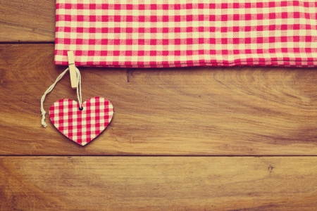 Retro toned background with checked tablecloth and heart shape on wooden board Stock Photo - 21736202