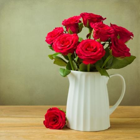 flores de cumpleaños: Rose ramo de flores en jarra sobre la mesa de madera