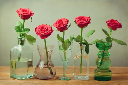 Rose flowers in vases, bottles and glasses  Still life composition