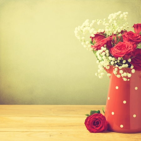 roses in vase: Rose flower bouquet in red polka dots jug with copy space Stock Photo