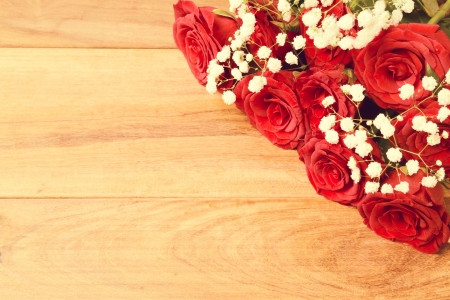 Wooden background with red roses and copy space