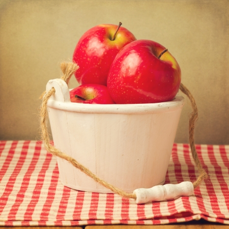 Fresh red apples in wooden bucket over checked tablecloth Stock Photo - 21736222