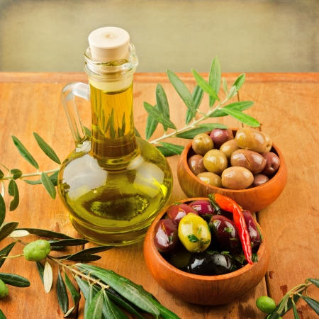 Olives and oil on wooden table Stock Photo - 21717423